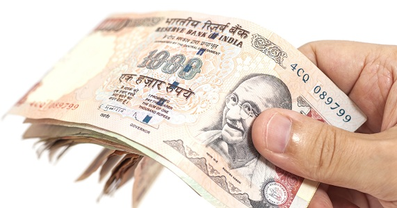 Hand with Indian thousand rupee notes